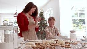 Madre juguetona e hija que hacen las galletas de la Navidad metrajes