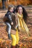 Madre juguetona que da a cuestas paseo a su hijo Imagen de archivo libre de regalías