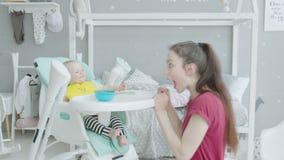 Madre juguetona que hace risa del bebé durante la alimentación metrajes