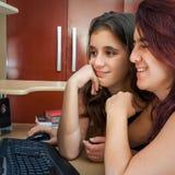Madre latina e la sua figlia che per mezzo di un calcolatore Immagine Stock