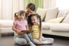 Madre linda con sus 2 años de la pequeña hija y 5 años de la hija que juega con la tableta digital en casa Fotos de archivo