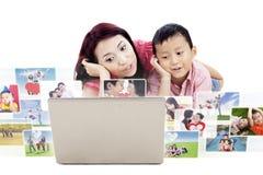 Madre linda e hijo que miran las fotos en el ordenador portátil Fotos de archivo libres de regalías