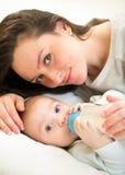 Madre linda en casa que alimenta al hijo del bebé con una leche Foto de archivo