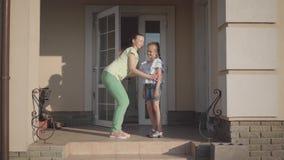 Madre linda joven del retrato que besa su situación adorable de la hija en el pórtico de una casa grande El abrazo del niño almacen de video
