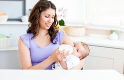 Madre linda que introduce a su bebé en la cocina foto de archivo libre de regalías