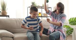 Madre loca con el hijo que se divierte en el sofá almacen de metraje de vídeo
