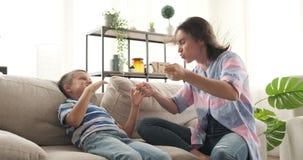Madre loca e hijo que se divierten en el sofá almacen de metraje de vídeo