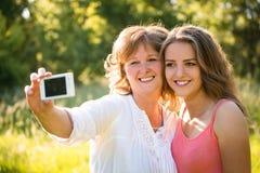 Madre mayor con el selfie de la hija Imagen de archivo libre de regalías