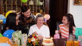 Madre mayor con la hija y las nietas en la fiesta de cumplea?os almacen de metraje de vídeo