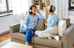 Madre mayor e hija adulta con los auriculares imagenes de archivo