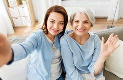 Madre mayor e hija adulta que toman el selfie fotografía de archivo libre de regalías