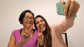 Madre mayor e hija joven de la raza mixta que hacen la foto divertida de Selfie con el teléfono móvil 4K almacen de metraje de vídeo