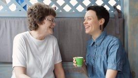 Madre mayor e hija joven que hablan en el sofá, sonriendo y comiendo café junto Familia feliz almacen de video