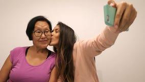 Madre mayor e hija joven que hacen la foto de Selfie con el teléfono móvil 4K almacen de metraje de vídeo