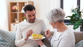 Madre mayor e hijo adulto que comen la torta en casa almacen de metraje de vídeo