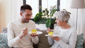 Madre mayor e hijo adulto que comen la torta en casa metrajes