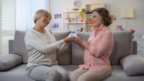 Madre mayor que da el presente al sofá casero que se sienta de la hija, proximidad de las relaciones almacen de video