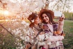 Madre mayor y su hija adulta que abrazan y que toman el selfie en jardín floreciente Concepto del día del ` s de la madre Valores Imágenes de archivo libres de regalías