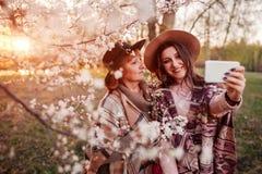 Madre mayor y su hija adulta que abrazan y que toman el selfie en jardín floreciente Concepto del día del ` s de la madre Valores Foto de archivo