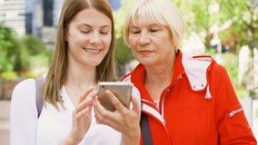 Madre mayor y su hija joven que se colocan en la calle usando smartphone Familia feliz junto