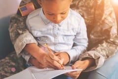 Madre militar con un niño en el revestimiento que hace notas Foto de archivo libre de regalías