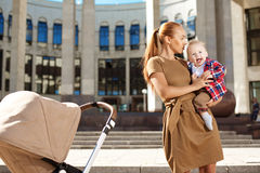 Madre moderna alla moda su una via della città con una carrozzina. Giovane Mo Fotografia Stock