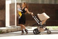 Madre moderna de moda en una calle de la ciudad con un cochecito de niño. MES joven Imágenes de archivo libres de regalías