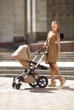 Madre moderna de moda en una calle urbana con un cochecito de niño. M joven Imagen de archivo libre de regalías