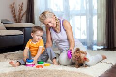 Madre, muchacho del niño y el jugar del perro de interior Fotos de archivo libres de regalías