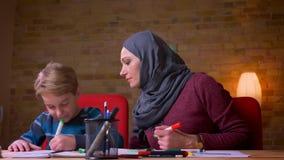 Madre musulmán alegre en el hijab que ayuda a su drenaje joven la imagen con los marcadores en atmósfera casera acogedora almacen de video