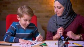 Madre musulmán alegre en el hijab que ayuda a su pequeño hijo a dibujar la imagen con los marcadores en atmósfera casera acogedor almacen de video