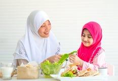 Madre musulmán discutir y enseñar sobre la verdura para la comida a su niña con el fondo blanco foto de archivo