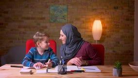 Madre musulmán en el hijab que ayuda a su hijo a dibujar la imagen con los marcadores en la tabla en atmósfera casera acogedora metrajes