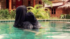 Madre musulmana con il bambino nella piscina archivi video