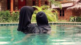 Madre musulmana con il bambino nella piscina stock footage