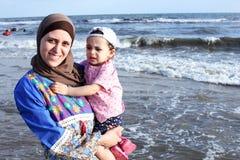 Madre musulmán egipcia árabe que celebra a su bebé asustado en la playa en Egipto Foto de archivo
