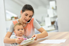 Madre occupata che alimenta il suo bambino e che parla sul telefono Fotografia Stock Libera da Diritti