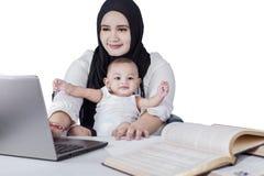 Madre occupata che per mezzo del computer portatile con il suo bambino Immagini Stock