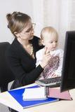 Madre ocupada con su bebé Imagenes de archivo