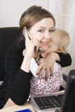 Madre ocupada con su bebé Foto de archivo