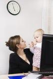 Madre ocupada con su bebé Fotos de archivo
