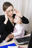 Madre ocupada con su bebé Fotografía de archivo libre de regalías