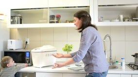 Madre ocupada en la cocina que toma cuidado de un bebé que hace el trabajo de la cocina almacen de video