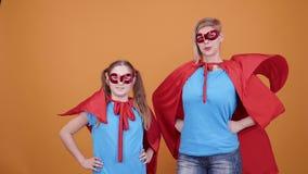 Madre orgullosa con su hija joven que se imagina para ser super héroes almacen de metraje de vídeo