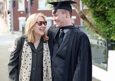 Madre orgullosa e hijo graduado de la universidad que sonríe y que abraza fotografía de archivo libre de regalías