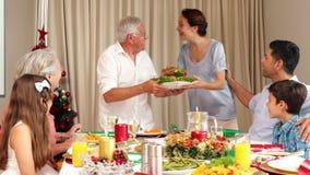 Madre orgullosa que trae el pavo de la carne asada a la tabla de cena de la Navidad almacen de video