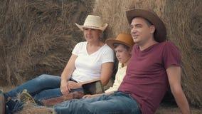 Madre, padre e figlio felici della famiglia con una compressa che si siede nel campo, appoggiantesi un fieno-rotolo Il concetto d stock footage