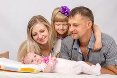 Madre, padre e hija, mirada de cinco años en el bebé recién nacido Fotos de archivo libres de regalías