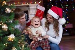 Madre, padre e hijo adornando el árbol de navidad Fotografía de archivo