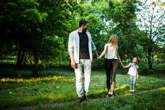 Madre, padre feliz y niña caminando en parque del verano y divirtiéndose Imagen de archivo